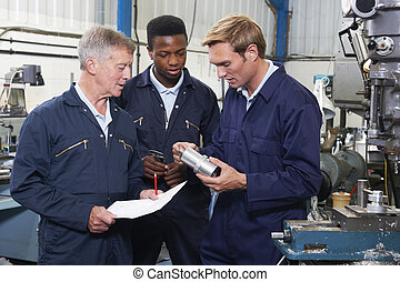 Team Of Engineers Having Discussion In Factory