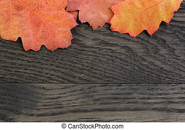 autumn background with red oak leaves on stained oak table,...