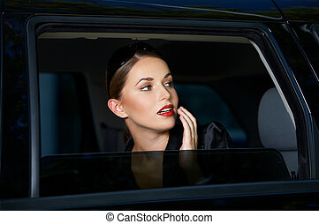 Sensual young woman looking out of a car window with parted...