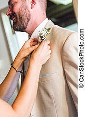 Wedding - Boutonniere pin up to grooms suit right before...