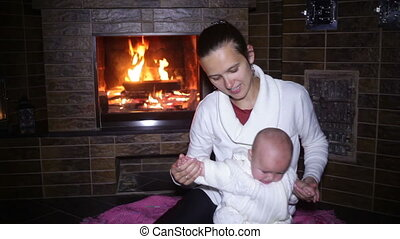 mother sitting with her baby near the fireplace at Christmas...