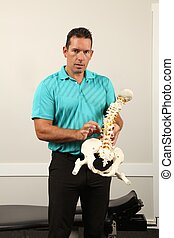 Chiropractor - A Chiropractor showing a model of the human...