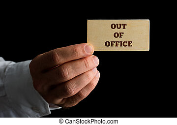 Man with a business card reading - Out of Office - Man...