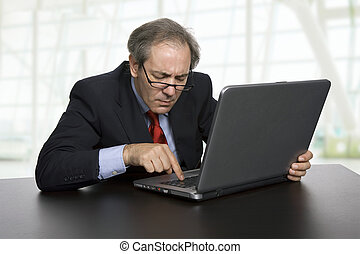 worried - mature businessman working with his laptop at the...