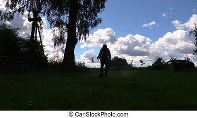 worker cut grass trimmer - Silhouette of villager cut grass...