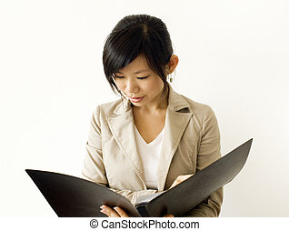 Research. - Asian girl reading document. For...