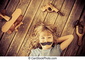 Feminism - Hipster kid with vintage wooden toys at home Girl...