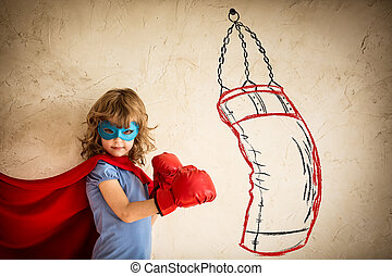 Winner - Superhero kid in red boxing gloves punching on the...