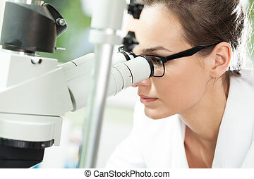 Scientist looking through microscope - Female scientist...
