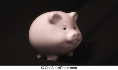 piggy bank on black background in her falling coins