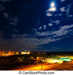 city skyline at night with stars clouds and copyspace