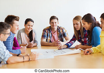 group of smiling students with blueprint - education,...
