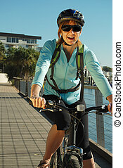 Boardwalk cycling - Female cyclist rides along the boardwalk...