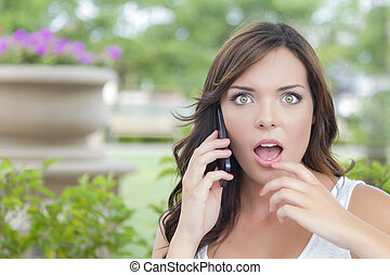 Shocked Young Adult Female Talking on Cell Phone Outdoors on...