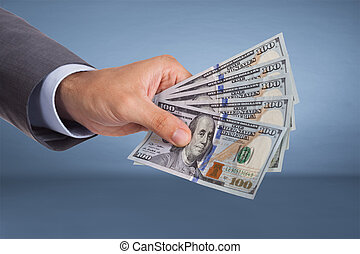 Hand holding paper currency over blue background
