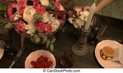 Cafes worker decorates festive table with flowers -...
