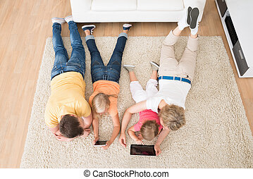 Kids Using Tablets Lying On Carpet At Home