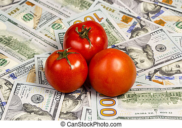 Tomatos on a dollars bills - Three ripe red tomatoes located...