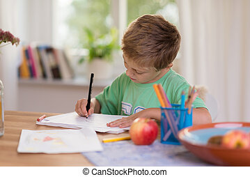 Young boy in school hard at work on his notes
