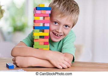 Cute happy little boy hugging a colorful tower on the dining...