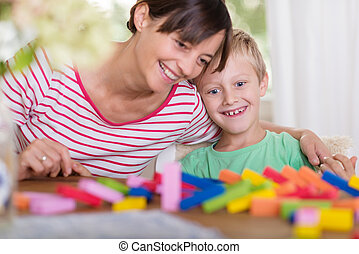 Young mother and son playing with building blocks - Young...