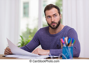 Man sitting thinking at his desk holding a sheet of paper in...