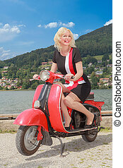 Young woman on a scooter - Young blonde woman having fun on...
