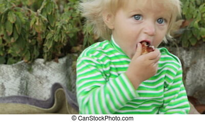 Girl child eats meat CU - Little girl eating a piece of...
