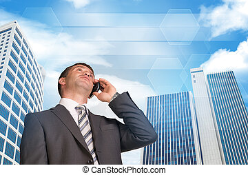 Businessman talking on the phone. Skyscrapers and sky with clouds