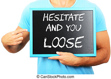 Man holding blackboard in hands and pointing the word HESITATE A