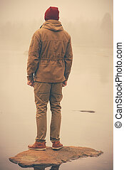 Young Man standing alone outdoor with foggy scandinavian...