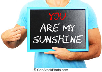 Man holding blackboard in hands and pointing the word YOU ARE MY