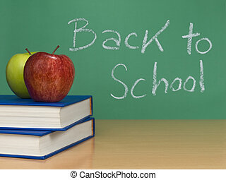 Back to school written on a chalkboard Two apples over books...