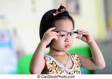 Little Asian girl wearing glasses.