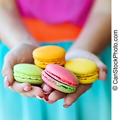 Girl holding colorful macaroons in hands - Girl holding...