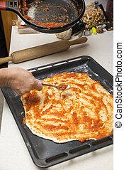 preparing the pizza dough with tomato