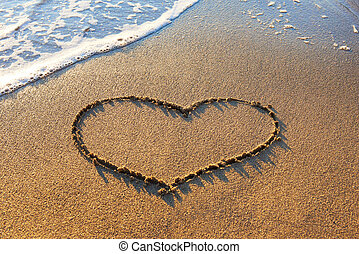 Heart on the sand - Heart drawn on the beach sand with sea...