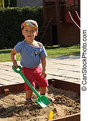 little boy in the sandbox - little boy playing in the...