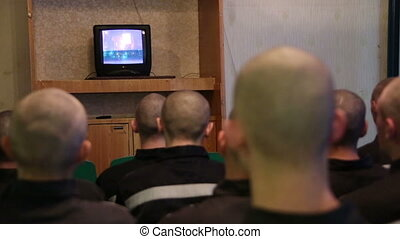 Prisoners and convicted persons watching TV - A group of...