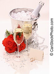 Two golden wedding rings, card, champagne glasses, red roses
