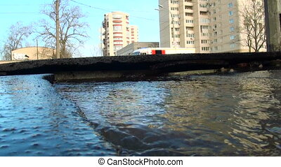 Water flows out from under the asphalt The accident rupture...