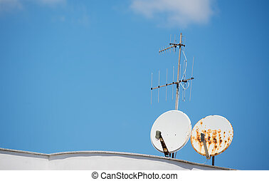 old dishes - old satellite dishes on a house roof