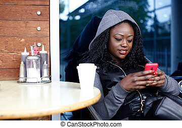 Smiling Woman Busy Text Messaging on Mobile Phone while...