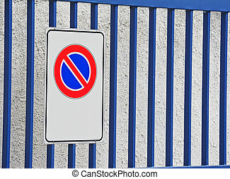 no parking sign with a blue gate in the background