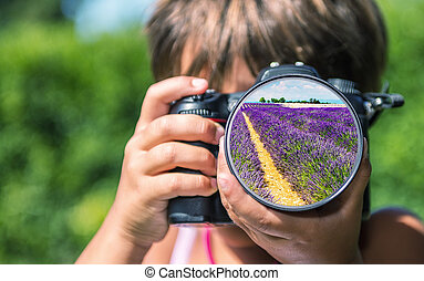 Young girl taking photos of lavender meadow by professional...