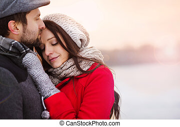 Winter couple hugging - Young couple hugging by the river in...