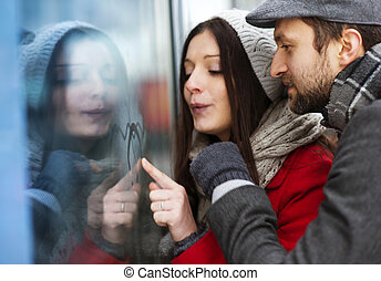 Winter couple - Young couple writing on steamed up window in...
