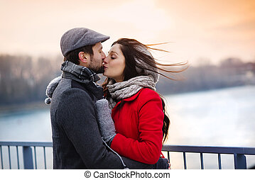 Winter couple kissing - Young couple kissing by the river in...