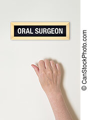 Female hand is knocking on Oral surgeon door for a medical...