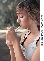 woman lighting a cigarette - young woman lighting a...